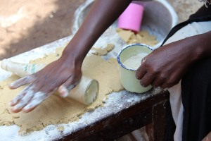 rolling out Cassava flour, bananas, and baking soda to prepare her pancakes for sale.